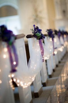 Church pews decked out with tulle and purple flowers