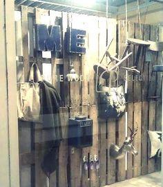 Wand met houten panelen waaraan je warme winterproducten hangt zoals sjaals, geweien, windlichten, plaids, kussens.