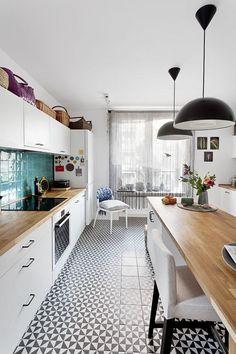 Lazurowe płytki nad blatem i czarno-biała mozaika na podłodze w kuchni