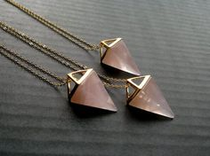 Rose quartz pyramid pendant on a gold plated chain. Measurements: Stone: Approximately 1 1/4 x 5/8 (32mm х 15mm), including the golden frame