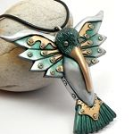 Green hummingbird with steampunk style rivets and straps on the wings for jewelry pendant or ornament