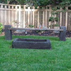 Hand Carved Lava Stone Firepit - Lava stone makes the perfect fire pit.  In this picture, our client dropped the rectangular shaped fire pit half way in to the ground.  Framed with grass, this natural gas fire pit provides hours of night time enjoyment for the family.  The bench seat is made from reclaimed teak rail road ties and the legs are also hand cut lava stone.