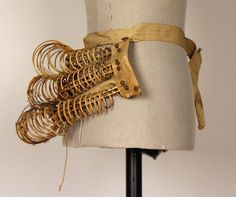 Date Made: 1884-1886, Bustle; metal wire coiled springs with front lacing. Three rows of cloth covered metal wire coils are secured to a front panel of fabric with lacing. Cotton waistband with metal.