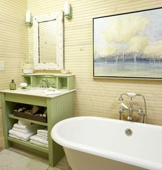 The master bath makes the most of its narrow floor plan with custom-painted vanities and a slipper tub lining one wall. Along with the tub, green glass sconces, pendant lighting, and beaded-board walls embrace vintage style. The bath is further serviced with a separate water closet and a pebble-tiled shower.