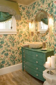 The tropical wallpaper is the perfect backdrop for this Teal Green dresser turned bathroom vanity and a very unique and decorative ivory sink