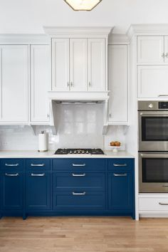 Blue lower and white upper cabinets and a custom hood add visual interest to this modern kitchen.