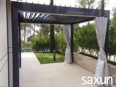 Pérgola de cuatro columnas en RAL 7024 que, para mantener la intimidad de sus usuarios, incorpora cortinas con riel en los laterales.