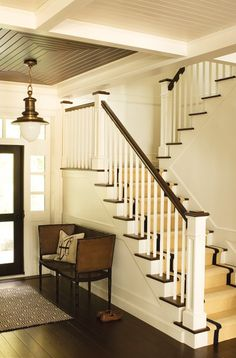 Another pinner said: Mix white painted paneling with a dark ceiling and trim for a fresh, nautical look in an entrance.    A brass ship's lantern and vintage cane-backed settee provide balance to the staircase's crisp palette, while a woven runner and David Hicks' graphic patterned door mat add texture and softness. The dark wood and white palette looks modern, but still nods to Colonial style.
