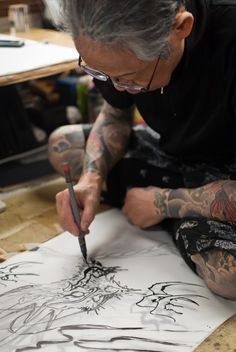 Japanese tattoo legend Horiyoshi III of Yokohama painting on rice paper, using traditional sumi-e techniques.