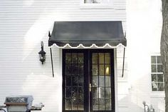 black awning with black french doors (and keepin' it real with a jakey looking grill)