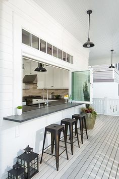 Kitchen pass through is fitted with glass folding windows fitted with a black…