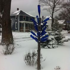 A bottle tree made from a branch, wooden dowels and blue wine bottles.