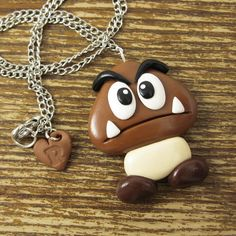 """Goombas are much less harmful when they are made of polymer clay. There's no need to have your star power activated when you wear this guy.  - hand sculpted high quality polymer clay - glazed for a nice shine - rapscallion signature heart charm - hangs on a 17"""" silver tone chain - NICKEL F..."""