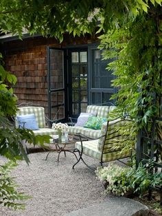 Gravel Patio       Cushions covered in an outdoor gingham fabric from Scalamandré brighten up the vintage wrought-iron seating on the patio of this Rhode Island retreat.