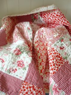 What a pretty pretty quilt in reds, white & cream with a little pink. floral and gingham prints.