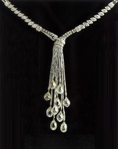 """A SPECTACULAR """"PAMPILLE BRIOLETTE"""" NECKLACE, BY VAN CLEEF & ARPELS Decorated at the front with cascading baguette-cut diamond and diamond collet tassels, each terminating with a briolette-cut diamond, suspended by a single and old european-cut diamond pierced cap, from the neckchain of alternately-set baguette and marquise-cut diamond segments, enhanced by rectangular-cut diamond spacers, mounted in platinum, one briolette-cut diamond deficient, circa 1930, with French assay marks…"""