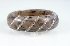 Scrumptous brownish gray marble clamper bracelet, made of lucite and inlaid with rhinestones. Bright, sparkly rhinestones, glossy lucite, this vintage bracelet is sure way to dress up your favorite grey jeans and ballet flats. Easy to use clamper style fits most wrists.  For dress up, casual or for collecting, this bracelet ticks all the right boxes!  Circa:1950s