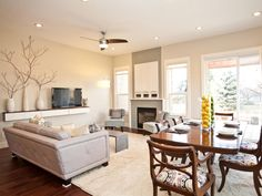 """This open concept living and dining room is comfortable and communal, making this space great for entertaining. Filling in the """"TV Hole"""" above the fireplace is functional pull-out storage. Updated finishes and light airy colors create a relaxing but warm environment."""