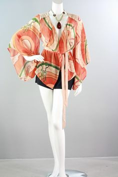 This Asian-inspired blouse is one of the hottest trends for this spring! It features open kimono sleeves, a gorgeous print with Asian motifs, horses, and chains. Drape the front panels around the waist with the included contrast belt for a stylish finish. Available in Small, Medium, Large. 100% Polyester $39.99