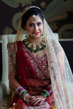 Bridal Portraits - Sonam | WedMeGood | Sonam wore a deep red lehenga for her wedding, with gorgeous meenakari uncut ruby and emerald necklace and matched it with green bangles and red chooda. Photo Courtesy : DKreate Photography #wedmegood #brides #lehenga #portraits