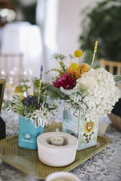 Vintage tin cans used as vases. Fun and fresh.