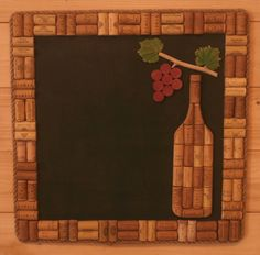 A chalkboard framed by an assortment of Greek wine corks.  Also a bottle, a bunch of grapes and two grapevine leaves add to the effect.
