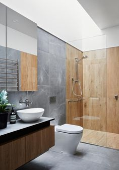 A Modern Grey And Wood Bathroom In this modern bathroom, a skylight brightens the space and highlights the wood-like tiles in the shower, and the grey tiles in the rest of the space. Bathroom Design Inspiration, Bad Inspiration, Modern Bathroom Design, Bathroom Interior Design, Modern Toilet Design, Toilet Tiles Design, Grey Modern Bathrooms, Toilet And Bathroom Design, Modern Bathroom Accessories