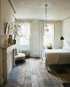 A peaceful earthy boho natural bedroom, rustic wood planks, antiques, and creamy whites, courtesy of John Derian