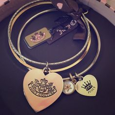 NIB Juicy Couture Bangle Set with Charms Really pretty Juicy Couture silver and gold bangle set of three with dangling charms! Comes in a lovely round pink gift box. Gold-colored bangle is plain with no charms, one silver bangle has ridges with a large silver heart charm, and the other silver bangle is smooth with a small silver heart charm and a round gold charm. Great paired together or mix n match with other bracelets. This would go well with the JC necklace in my closet! Would make a…