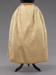 "Quilted petticoat ca. 1795 via The Costume Institute of the Metropolitan Museum of Art  ""Quilted petticoats were a part of informal dress throughout the 18th century. Initially, this type of petticoat served for warmth and to give shape to the lower half of the body in a way which would disguise the wearer's legs. As the skirts began to open in the front in the early 18th century women chose more decorative quilted petticoats to add another layer of detail."