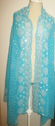 This is a gorgeous long Turquoise color scarf, with rich silver Metallic hand embroidery, the type women wear in India. There are also silver metallic sequins on it. The scarf is in new condition, and shows no signs of previous wear. I received it years ago as a gift from a client, and never wore it, it was stored in a plastic bag. This pretty scarf is from a smoke and pet free environment. Hand washable. The size is 82 inches on the longer side and 36 inches on the shorter side. There is…