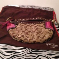 Unique Signature Coach small bag. Coach has made a small signature brown with pink purple maroon suede strip patterns on each side. The strap is brown leather with gold metal dots on it along.with the same on the top front and back . The purse charm is leather on one side and pink suede on the other. There is one zip pocket inside and it closes with tassels on the zipper. Preowned and some wear on the suede. Another one of coaches excellent pieces. Coach Bags Mini Bags