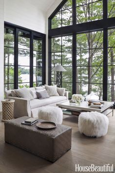 In the living room of an Ontario cottage, a 20-foot-high wall of windows provides sweeping vistas of Lake Joseph. Designer Anne Hepfer had the ottoman in the foreground custom made using vintage woven mats from Borneo.