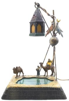 Lot 2165  A Cold Painted Cast Metal Orientalist Table Lamp,  in the form of two figures with camels beneath a lantern suspended over a slag ...