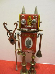 Damien Devil Bot – This is a one of a kind found object robot sculpted by Cheri Kudja.