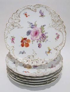 Sechs Teller Nymphenburg, um 1895. Reliefierter Rocaillerand mit Durchbruch. Bunter Blumendekor. Go — Porzellan