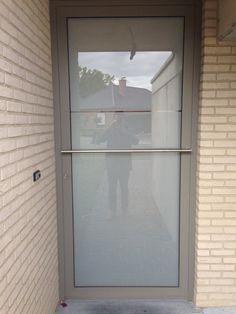 Voordeur in aluminium. Profielreeks Reynaers: CS 77-HI. Beglazing: Climaplus One warm edge.  Matte ruit (gezandstraald) met een klaar lijntje op ooghoogte. Inox deurtrekker, horizontaal geplaatst.