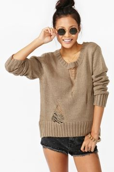 Awesome taupe knit featuring shredded detailing and an asymmetric hem. Ribbed at neckline, cuff and hem. Perfect paired with denim shorts and
