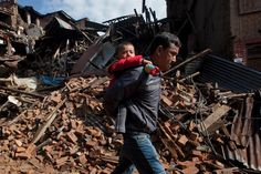 A Nepalese man carries a child as he walks past destroyed buildings that collapsed in Saturday's earthquake, in Bhaktapur, on the outskirts of Kathmandu, Nepal on April 27, 2015.