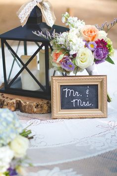 bride and groom table sweetheart table centerpiece lantern wooden stump led candles mr. & mrs. chalkboard frame gold bridal bouquet purple white green blue peach lace overlay tablecloth