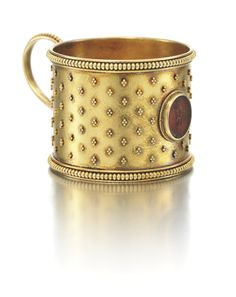 A FABERGÉ MINIATURE GOLD TEA GLASS HOLDER, WORKMASTER ERIK KOLLIN, ST PETERSBURG, CIRCA 1885 in Scythian taste, cylindrical, the matte-finish surface applied with clusters of granulated gold beads, the front with an Antique carnelian intaglio of Mars, gadrooned borders and scroll handle, struck with workmaster's initials, 56 standard height: 3.2cm, 1 1/4 in.
