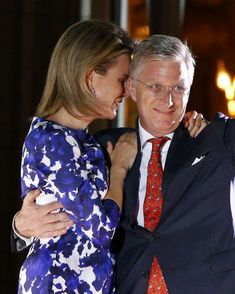 Belgium's King Philippe hugs Queen Mathilde as he waves from the balcony of the Royal Palace in Brussels this evening.