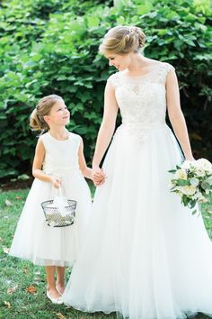 Sweet bride + flower girl moment: http://www.stylemepretty.com/south-carolina-weddings/2016/01/25/organic-industrial-wedding-at-701-whaley/ | Photography: Marcie Meredith - http://marciemeredith.com/