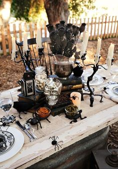 """Loving this """"Bone Appetit"""" Halloween Dinner Party with skull plates, antique books, spider web coasters, black chairs, speared donut holes, and skeleton favor bags."""
