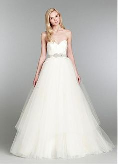 The bodice is embellished with over lace ,while the skirt is made of tulle and lining is made of satin. It features sweetheart neckline and raised waistline adorned with beaded rhinestones belt in a-line silhouette. The back is zipper up closure.
