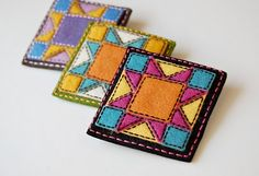 tiny quilt blocks out of felt and embroidery floss.