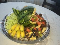 Melonen-Hai Die Melone durchschneiden, so dass die eine Hälfte etwas größer als die andere Hälfte ist. Die größere Hälfte nun aushöhlen und das Fruchtfleisch in mundgerechte Stücke schneiden und beiseite legen.  Die ausgehöhlte Melonenhälfte auf einem Teller platzieren. An der Oberseite wird nun ein ca. 10cm langes und 5-8cm breites Maul eingeschnitten (je nach Größe der Melone werden die Maße angepasst). Am Maulrand ringsherum einen etwa 1cm breiten Rand von der grüne Melonenschale…