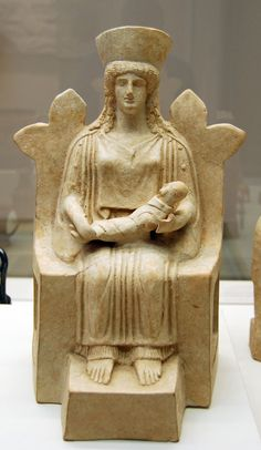 Terracotta figure of a woman seated on a throne, holding a tightly-wrapped baby.  Made in Boeotia, c. 450BC