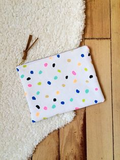 White cotton canvas pouch with hand painted multicolored spot print all over. Black metal zipper closure with leather pull. Fully interfaced and