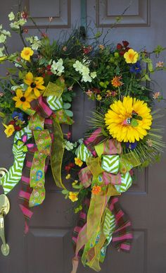 Spring/summer wreath with blackeyed susan, white cherry blossoms, large daisy. It has all bright colors of gold, pink, purple, blues, greens. Wonderful combination of funky ribbons.